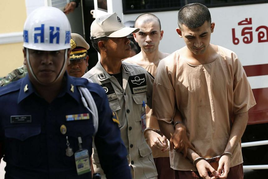 Yusufu Mieraili (right) and Adem Karadag (second from right) are escorted by police officers and prison personnel as they arrive at the Military Court in Bangkok on April 20, 2016.