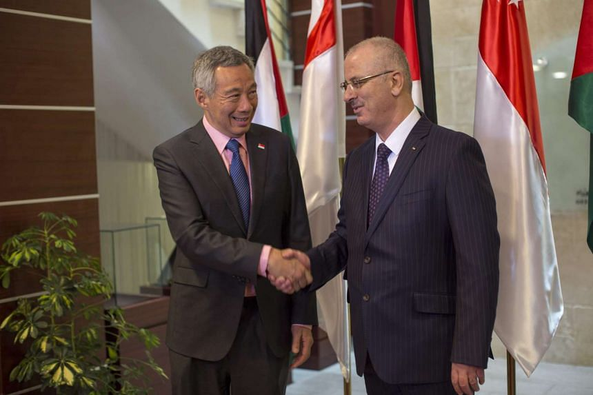 Palestinian Prime Minister Rami Hamdallah (right) shakes hands with Singapore Prime Minister Lee Hsien Loong during his visit to the West Bank town of Ramallah on April 20, 2016.