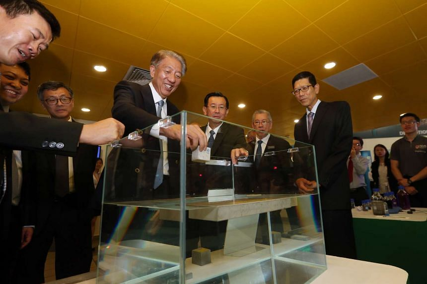 Deputy Prime Minister Teo Chee Hean (fourth from left) tests out a piece of floating concrete as part of a waste-to-resource project that involves fast track volmetric construction using lightweight high performance materials.