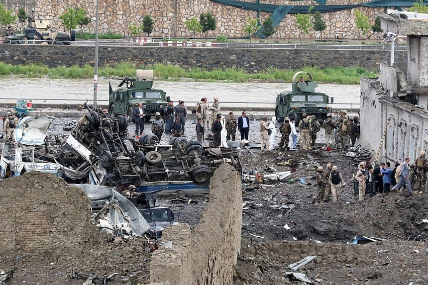 Afghan security officials inspecting the site of a suicide bombing in Kabul yesterday. Taleban militants, who last week launched their annual spring offensive, claimed responsibility for the attack. A girl injured in yesterday's suicide bomb blast in