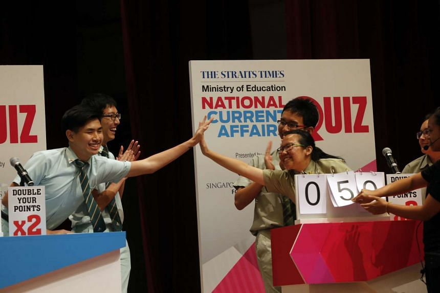 Tampines JC students (left) gave Temasek JC students a high five during the Big Quiz on April 20, 2016.