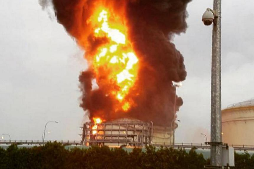 Fire and plumes of smoke are seen rising from an oil tank on Jurong Island, on April 20, 2016.