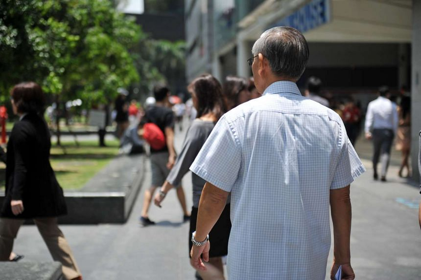 An elderly man walking in the Central Business District area in Singapore.
