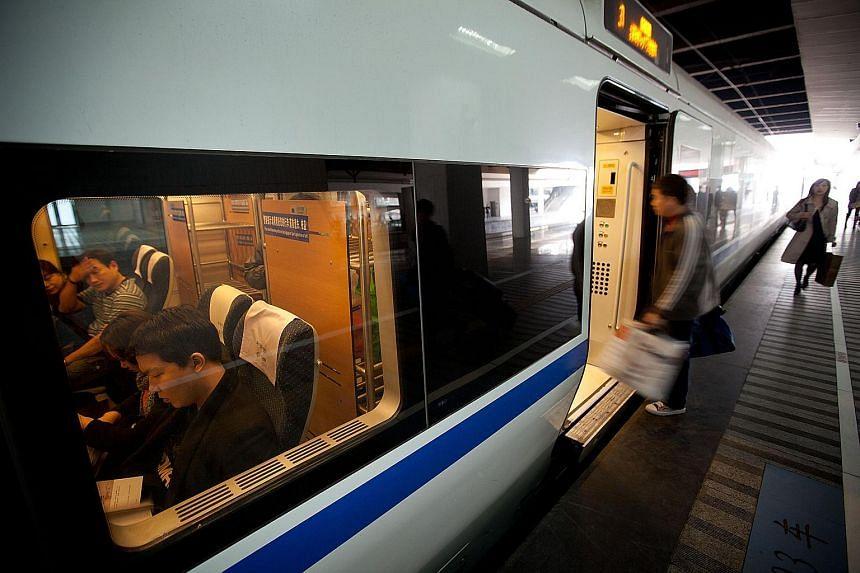 Passengers board a Shenzhen to Guangzhou China Railway high-speed train at the Luohu railway station in Shenzhen.
