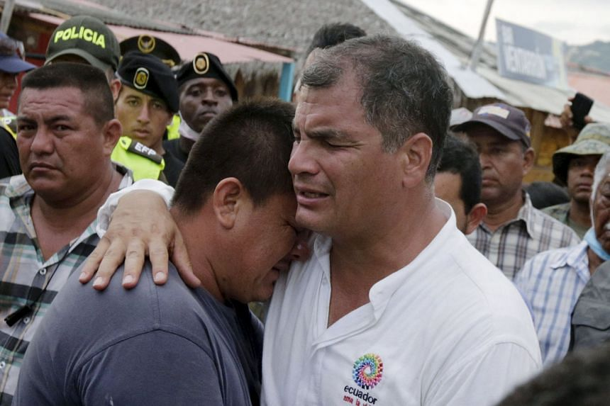 President Correa comforting a resident in the town of Canoa, Ecuador, on Monday. People have taken to looting, taking things such as clothes, shoes, aluminium window frames and cables, in hopes of selling the materials. Economic growth forecasts are near