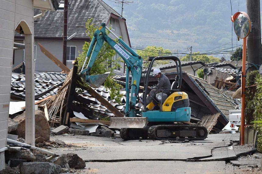 A worker controls a backhoe beside collapsed houses in Mashiki, Kumamoto prefecture on April 19, 2016.