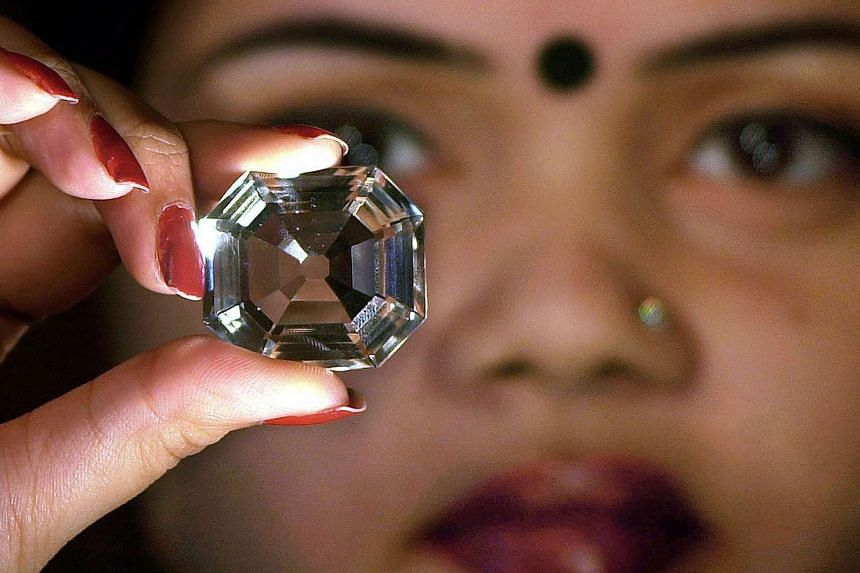 An Indian model holding up a replica of the famous Indian Koh-i-Noor diamond in Calcutta.