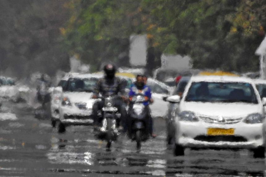 Vehicles are seen driving through a heat haze in Chandigarh, India, on April 20, 2016.