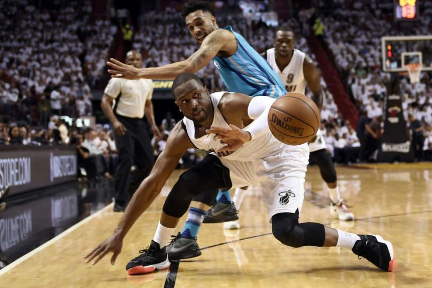 Miami Heat guard Dwyane Wade (front) and Charlotte Hornets guard Courtney Lee battle for the ball during their NBA play-off game in Miami on April 20, 2016.