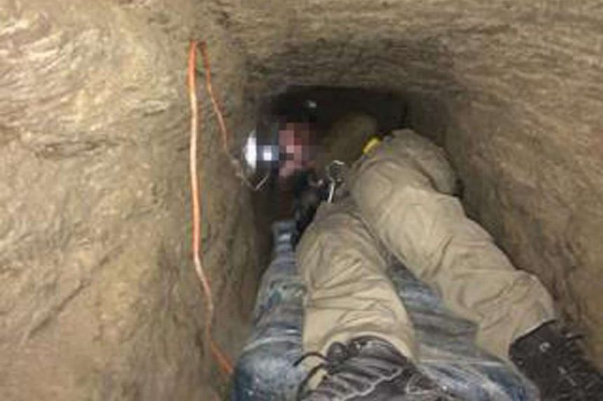 A US security officer showing the media the narrow tunnel, which was used for drug trafficking.