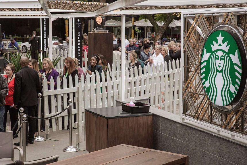 Hundreds of people queue during the official opening of South Africa's first Starbucks store in Johannesburg on April 21, 2016.