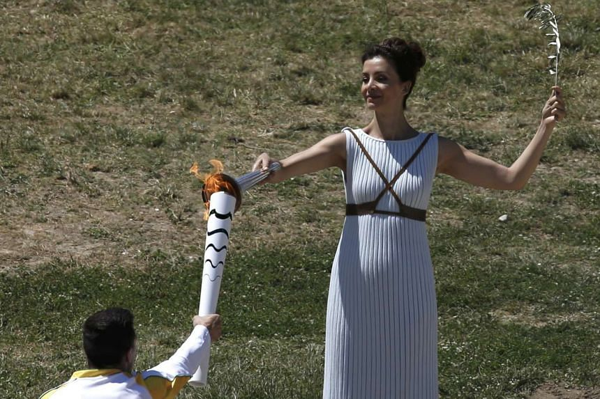Greek actress Katerina Lehou, playing the role of High Priestess, passes the Olympic flame to the first torch bearer, Greek gymnast Eleftherios Petrounias on the site of ancient Olympia, Greece on April 21, 2016.