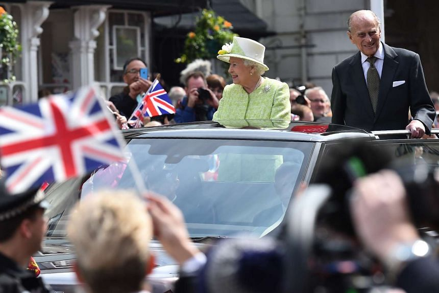 Britain's Queen Elizabeth II (left) accompanied by Prince Philip, Duke of Edinburgh, greet wellwishers during a walkabout on her 90th birthday in Windsor on April 21, 2016.