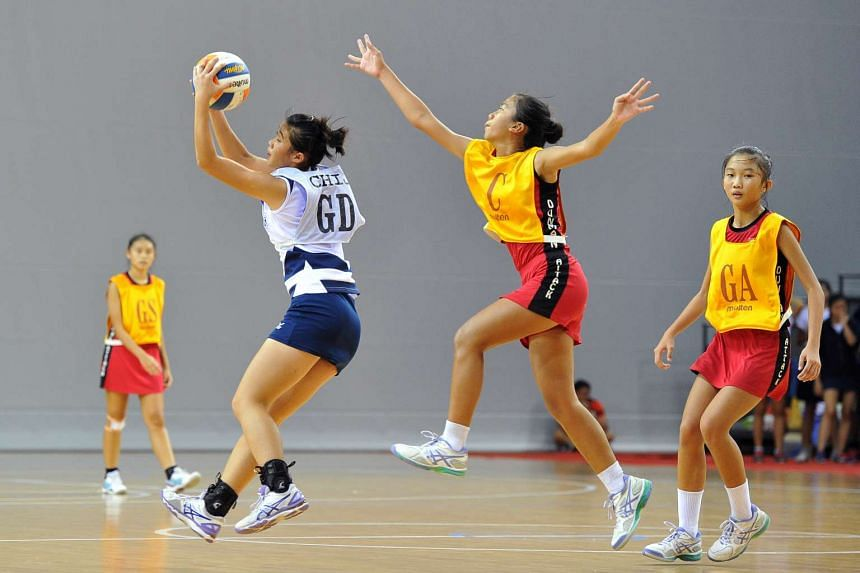 Cythnia Ang from Dunman Secondary School (second from right) fighting for the ball with CHIJ Secondary School's Alena Rae Ong (second from left).