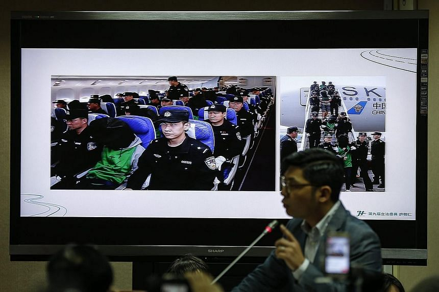 Taiwanese fraud suspects, (above, in masks) being escorted at Taoyuan Airport by Taiwanese police after being deported from Malaysia last Friday and (below, in hoods) being deported from Kenya to China as displayed on a monitor during a Taiwanese leg