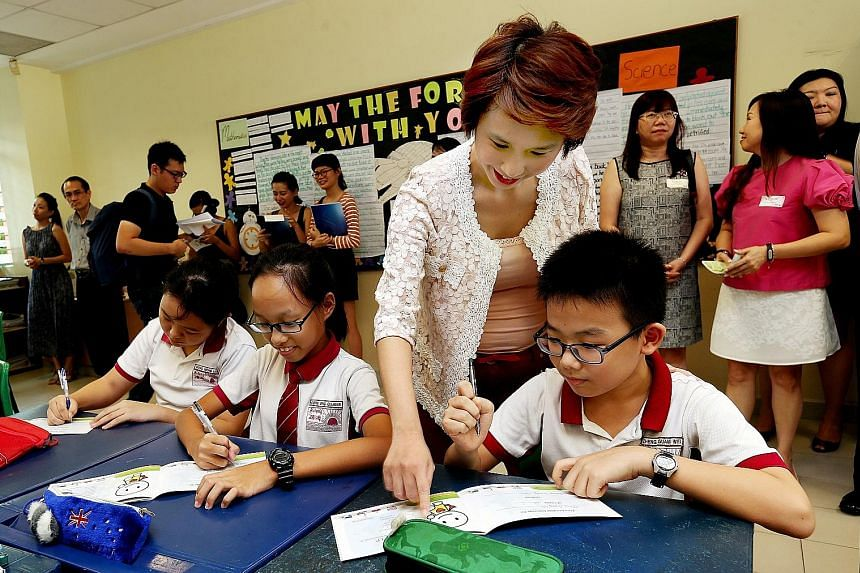 """Ms Low with Rulang Primary School pupils Dora Ong Qianxue (second from left) and Zheng Gang Wei (right) at the launch of the Values in Practice programme yesterday. The pupils are using programme booklets that contain """"missions"""" for pupils, through w"""