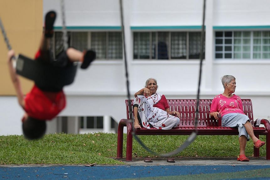 Senior citizens hang out at a bench next to a playground in Bukit Batok Central.
