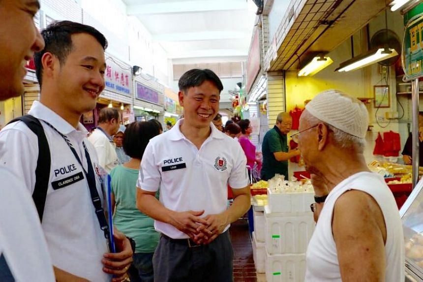 MP Louis Ng (middle) speaking to a resident in Nee Soon during his day-long experience as a police officer.