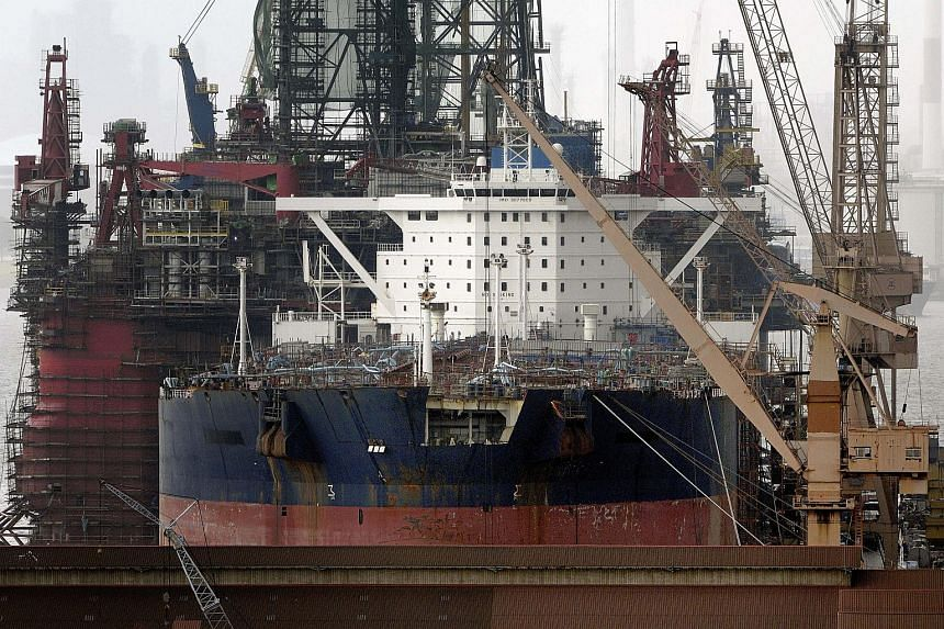 An oil tanker in the foreground and an oil rig in the back undergo repair at the Jurong Shipyard of Sembcorp Marine Ltd. in Singapore.