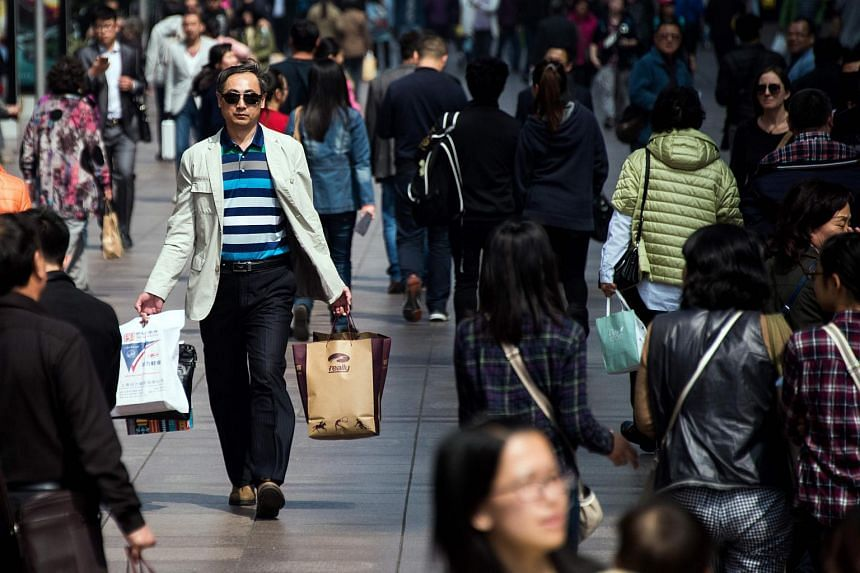 A man carries his shopping bags on a busy street in Shanghai.