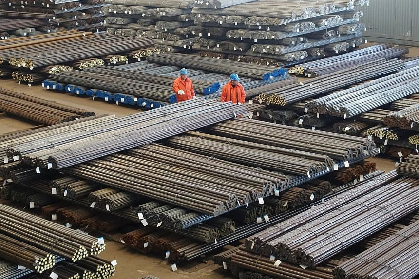 Workers check steel products at a factory in Dalian, China.
