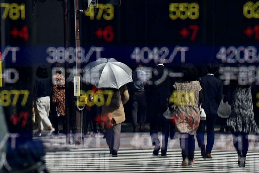 Pedestrians are reflected on an electric quotation board displaying the Nikkei key index of the Tokyo Stock Exchange in Tokyo.