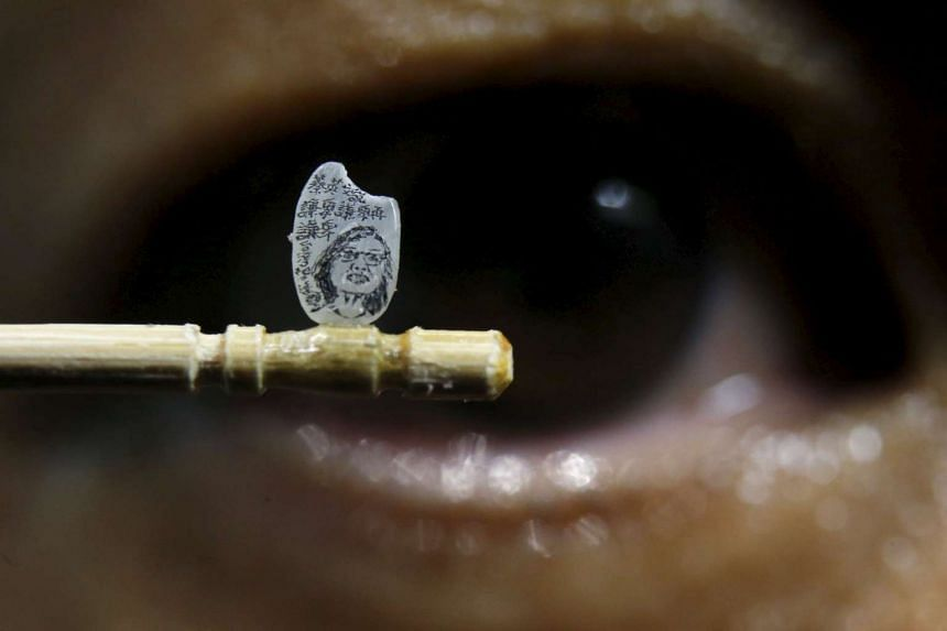 Miniature artist Chen Forng-Shean poses with his latest work, a miniature portrait of Taiwanese president-elect Tsai Ing-wen on a grain of rice, in Taipei, Taiwan on April 18, 2016.