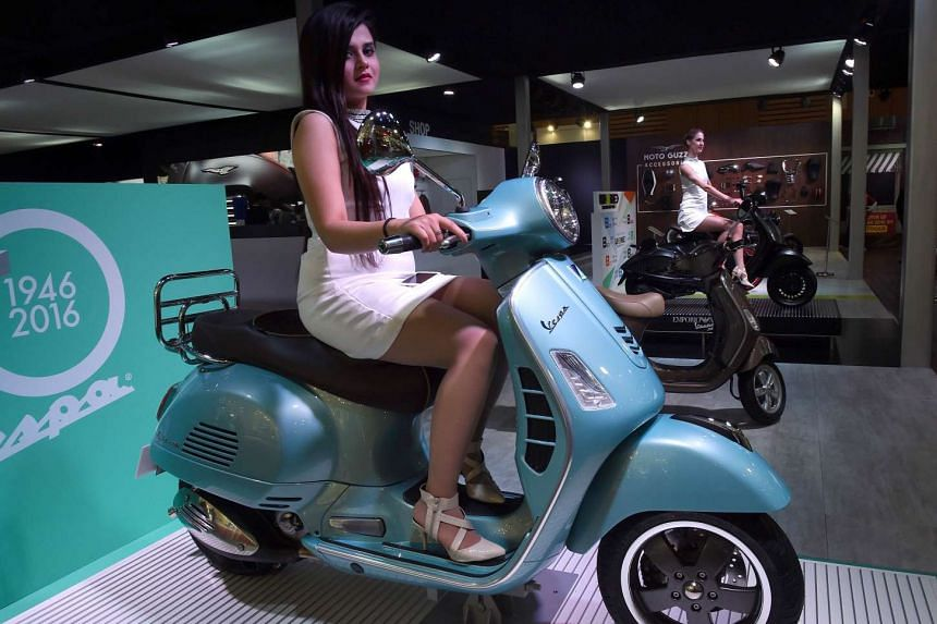 A model poses with a Vespa GTS 300 scooter at Auto Expo 2016 in Greater Noida, on February 4, 2016.