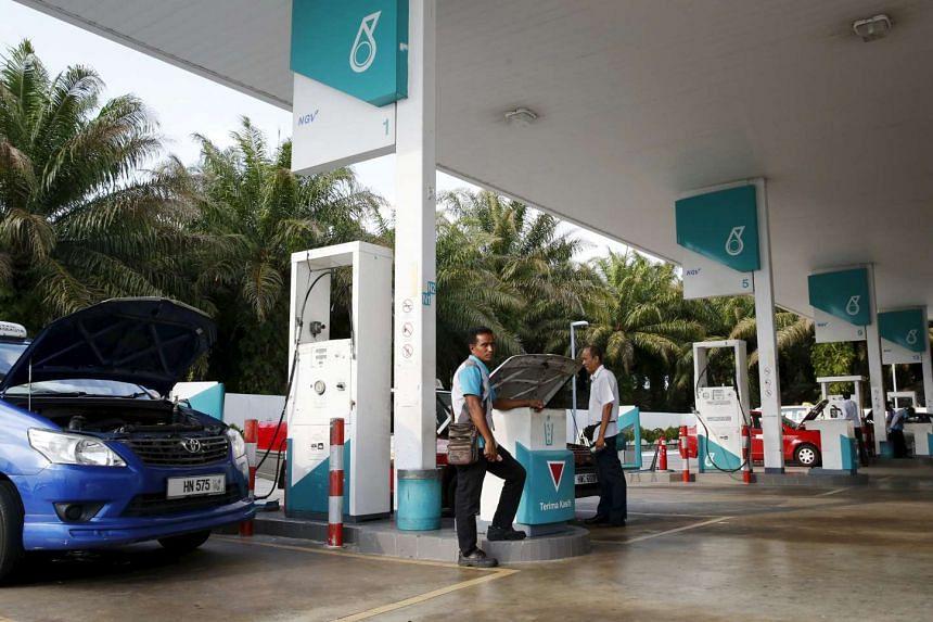 A pump attendant works at a Petronas petrol station outside Kuala Lumpur, Malaysia, on March 1, 2016.