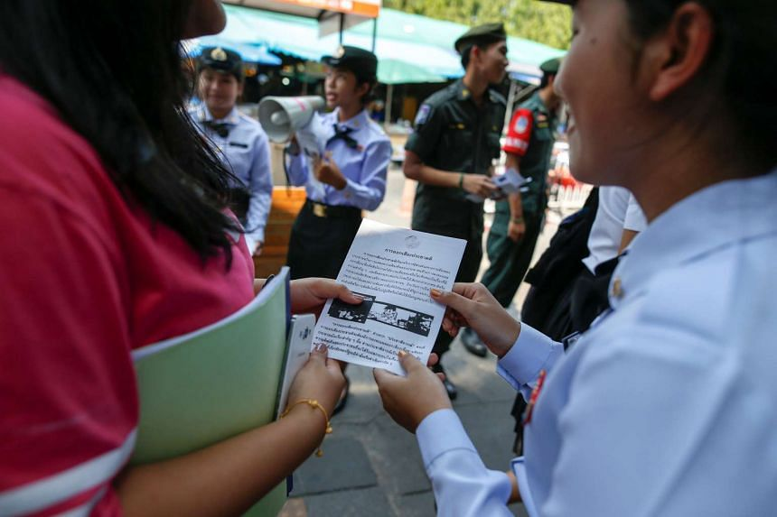 A student from the military's territorial defence programme offers a brochure during a military campaign to tell people to vote in the August referendum in Bangkok.