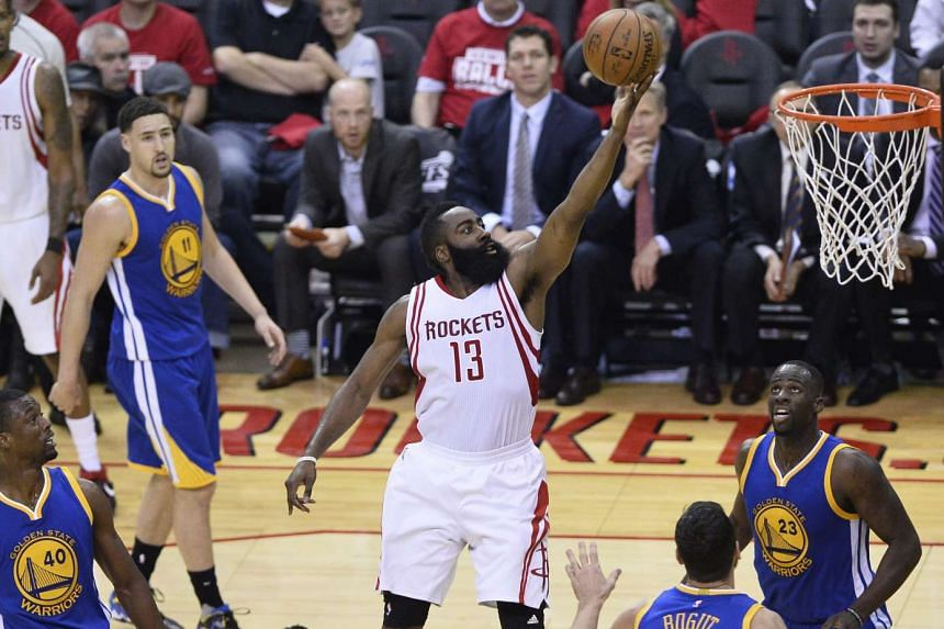 Houston Rockets player James Harden (centre) goes to the basket against the Golden State Warriors in the NBA Western Conference first round basketball game.
