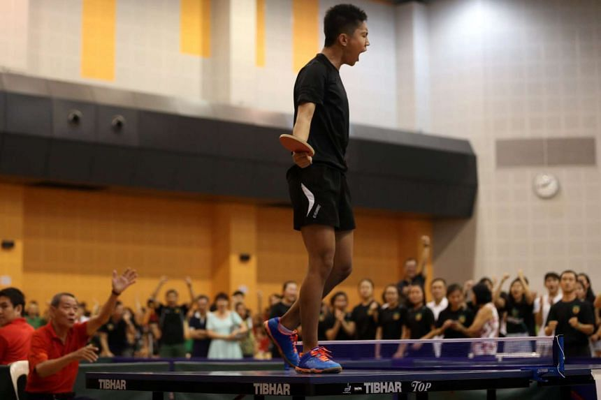 Raffles Institution paddler Ryan Goh jumps onto the table after winning his match against his Nanyang Junior College opponent at the A Division inter-school finals.