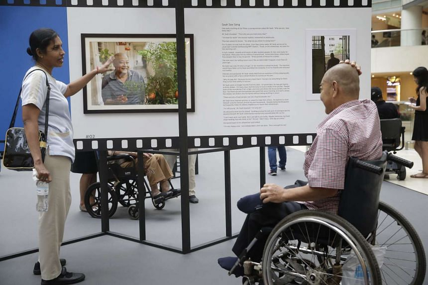 Mr Seah See Seng (right), a 62-year-old patient with Home Nursing Foundation, bashfully looks at his own portrait pointed out by HNF nurse clinician M. Kanagarani (left) at the Portraits of Love exhibition.