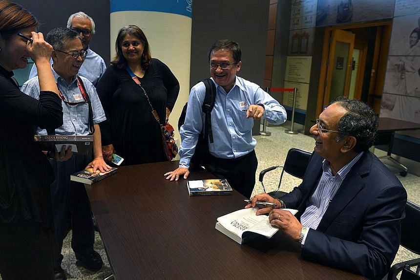 (From left) Mr Patrick Daniel, editor-in-chief of Singapore Press Holdings' English/Malay/Tamil Media group, Mr Goh, Mr Velloor and Mr Fernandez at the book launch. Mr Velloor (far right) signing copies of his book (above), India Rising: Fresh Hope,