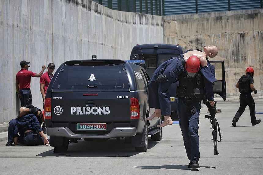 """Spear's Staff Sgt Mu (with rifle) and his teammates evacuating """"casualties"""" in Operation """"Man-down"""" as part of the Asian Prisons Lockdown Challenge, a biennial event organised by the Singapore Prison Service for its regional counterparts. The Spear t"""
