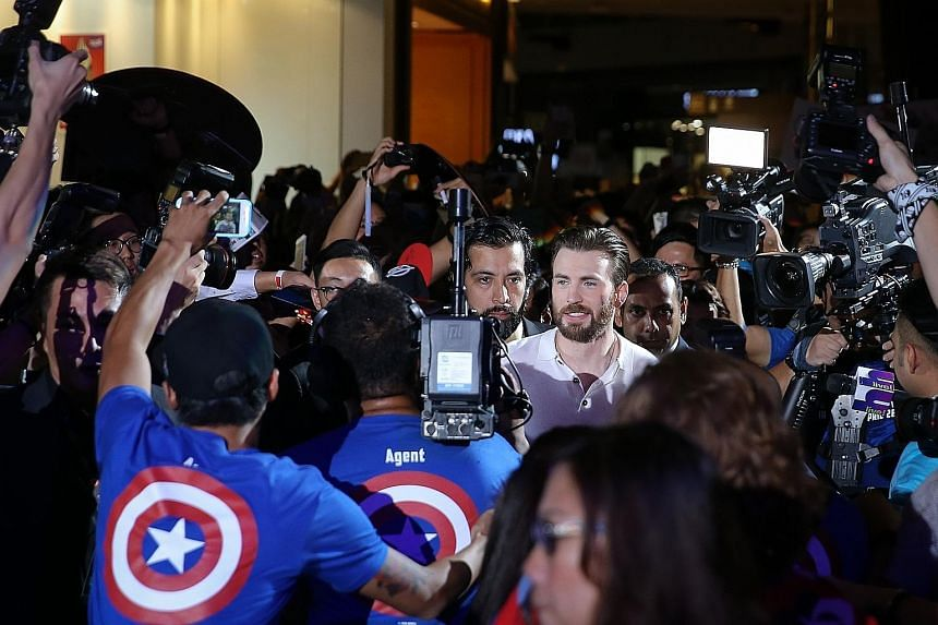 Thousands of Marvel Comics and movie fans crowded all four floors of Marina Bay Sands' shopping mall last night to catch a glimpse of Hollywood heart-throb Chris Evans (left) and his Captain America: Civil War co-stars Anthony Mackie and Sebastian St