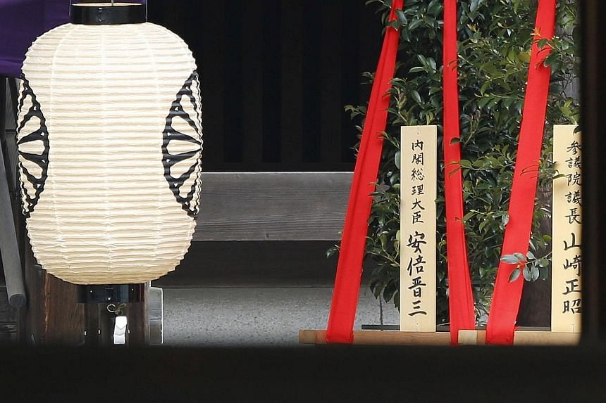 """A wooden sign reading """"Prime Minister Shinzo Abe"""" is seen on a masakaki tree - a ritual offering - from Mr Abe at the controversial Yasukuni Shrine for war dead in Tokyo yesterday. China and South Korea had suffered under Japan's occupation and colon"""
