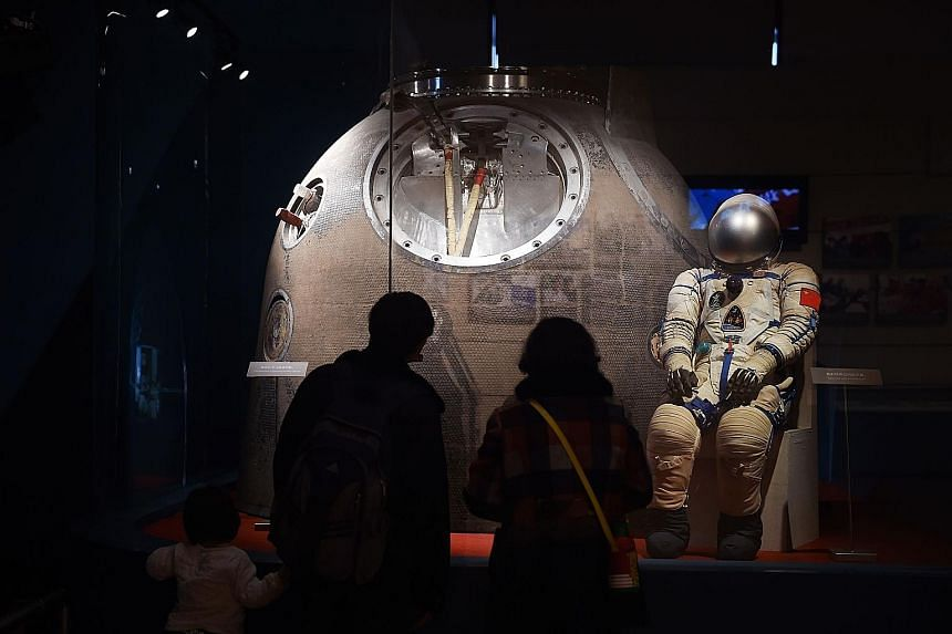The spacesuit and Shenzhou 5 re-entry capsule used by Mr Yang Liwei, China's first astronaut in space, on display at an exhibition in Beijing in March. China is trying to develop its space programme, but is still playing catch-up with the US and Russ