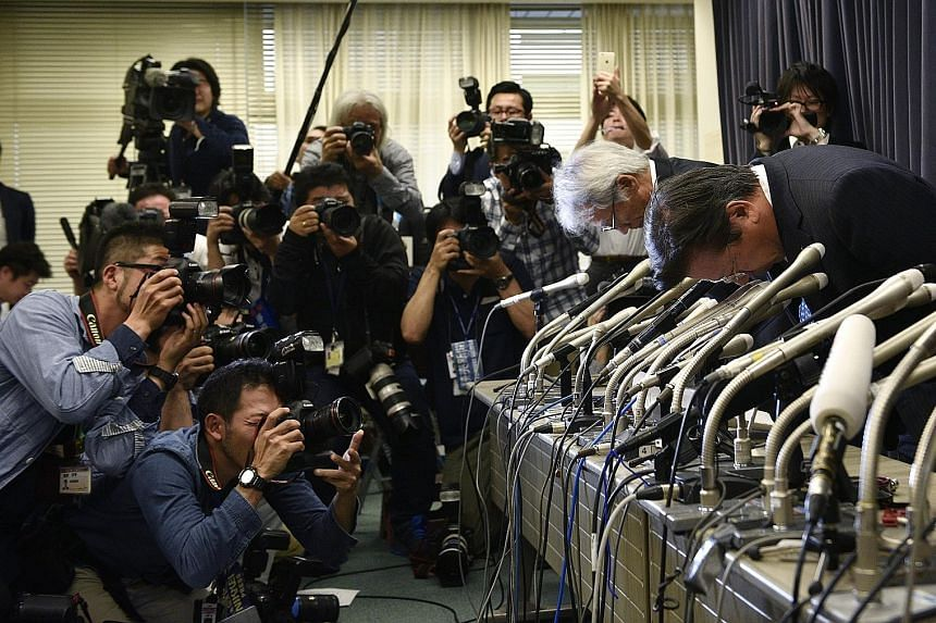 Mitsubishi Motors president Tetsuro Aikawa (right) and vice-president Ryugo Nakao bowing at a press conference on fuel efficiency tests in Tokyo on Wednesday.