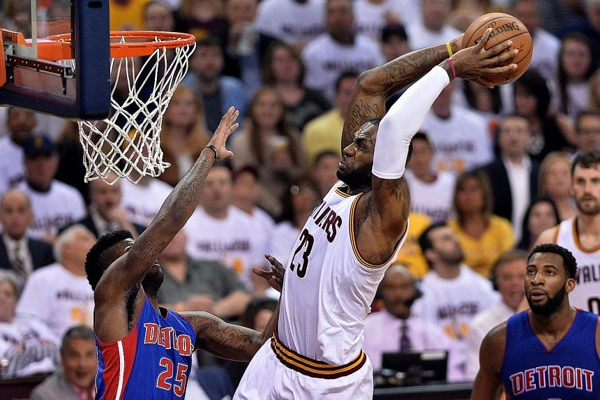 Cleveland's LeBron James (23) slam dunks over Detroit's Reggie Bullock during the Cavs' 107-90 victory on Wednesday. The Pistons had no answer to James' power and great three-point shooting from J.R. Smith, Kyrie Irving and Kevin Love.