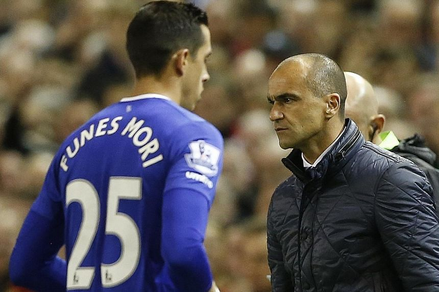 Defender Ramiro Funes Mori walking past an angry Everton manager Roberto Martinez after being sent off for a bad tackle on Divock Origi.