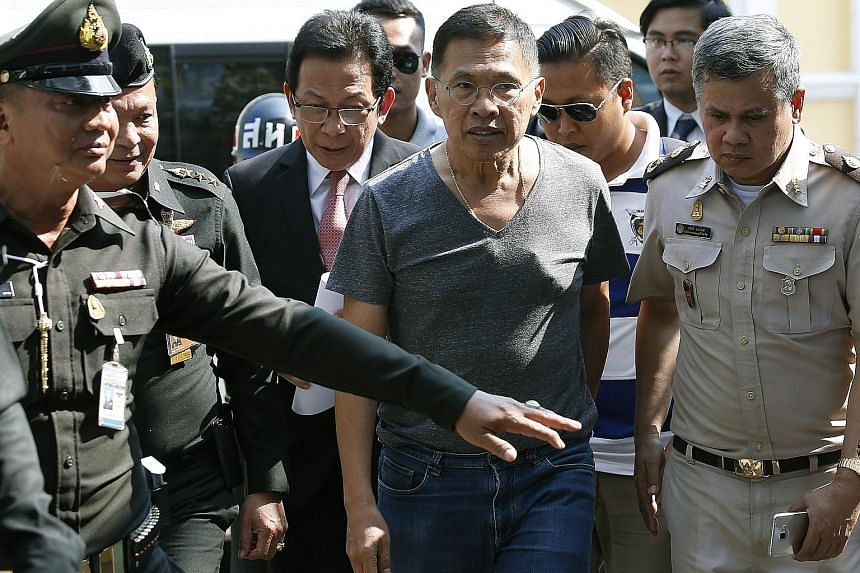 Mr Watana Muangsook (centre), who was minister of social development in a Thaksin government, being escorted by military officers as he arrived at the Military Court in Bangkok yesterday. He was taken into military custody on Monday for criticising t