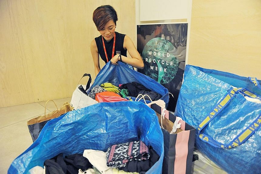Store employee Siti Farrah Umaina showing old clothes collected at H&M's outlet in Orchard Building. During H&M's World Recycle Week, donors will receive two 15 per cent discount vouchers for each bag of old clothes.