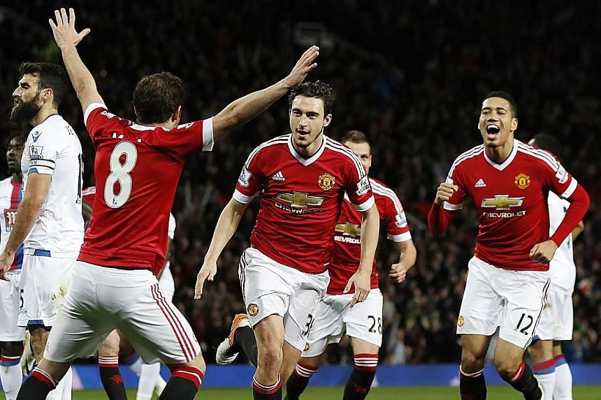 Matteo Darmian (centre) celebrates with Juan Mata (No. 8) and Chris Smalling (No. 12), after scoring United's second goal to seal a 2-0 win over Crystal Palace. Both sides will play in FA Cup semi-final ties this weekend.