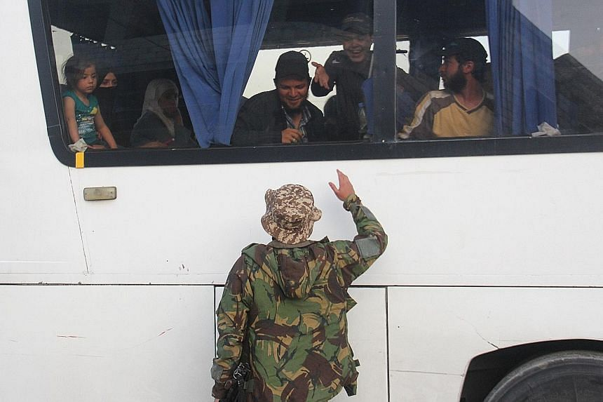 A Syrian fighter greeting medical evacuees and their families as a convoy of buses and ambulances from the Syrian villages of Zabadani and Madaya arrived on the outskirts of Idlib yesterday during an operation to evacuate hundreds of wounded people f