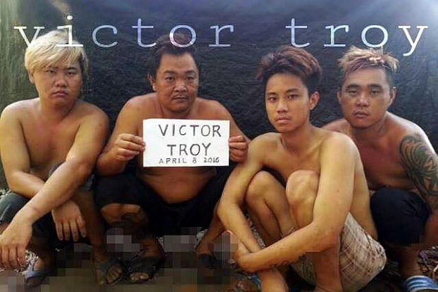 """The four Malaysians said to have been kidnapped by the Abu Sayyaf on April 1. """"Victor Troy"""" in the sign refers to a Facebook account under the name """"Victor Troy Poz"""", where the image was first loaded. Police are investigating the account's owner."""