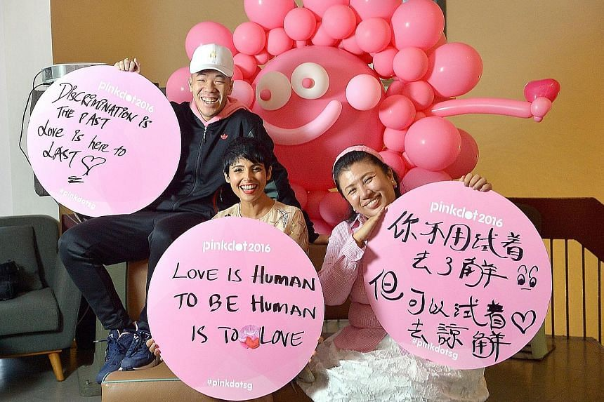 Pink Dot 2016 ambassadors (from left) rapper ShiGGa Shay, TV host Anita Kapoor and actress Liu Ling Ling with their self-written placards. Although some participants may write pro-LGBT messages that could alienate mainstream society, Pink Dot spokesm