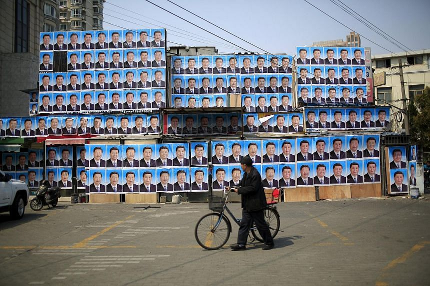 A man with a bicycle walks past a building covered in hundreds of posters of Chinese President Xi Jinping in Shanghai, China, on March 26, 2016.