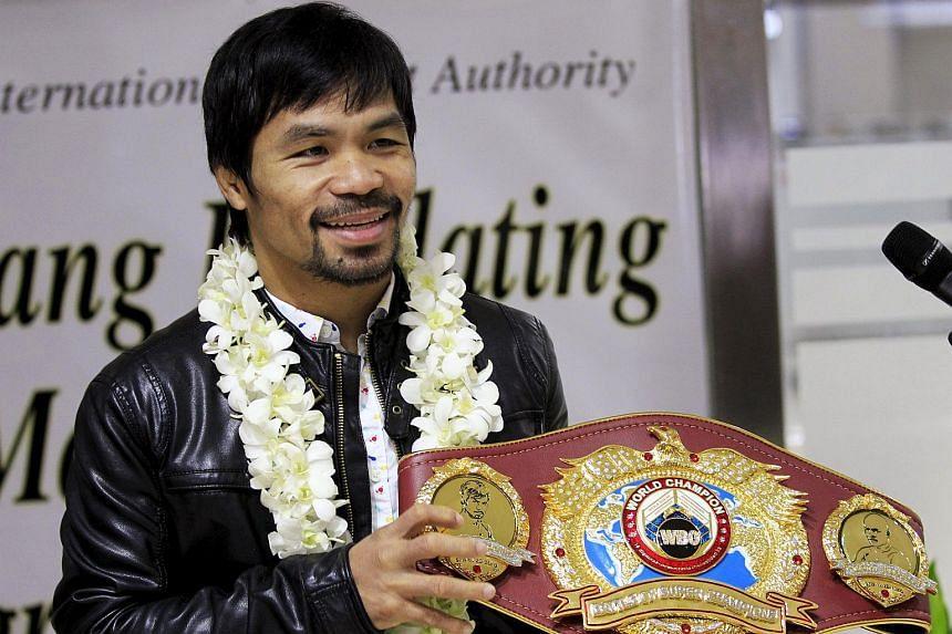 Filipino boxing champion Manny Pacquiao shows his WBO championship belt in Manila, on April 14, 2016.