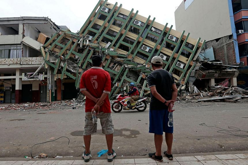 Men look at a destroyed building in the town of Portoviejo, Ecuador, on April 21, 2016.